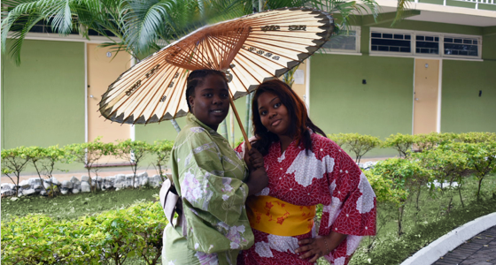 Students dressed in Japanese outfits with umbrella