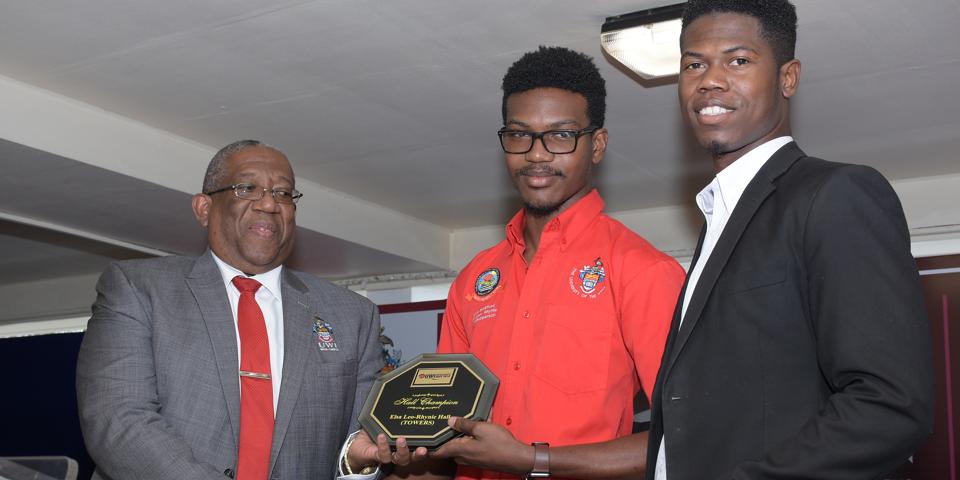 Principal awarding student with Hall Champion Plaque