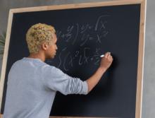 Teacher at blackboard doing math equation