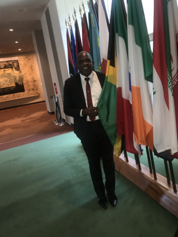 Senator Floyd Morris beside flag of Jamaica at UN